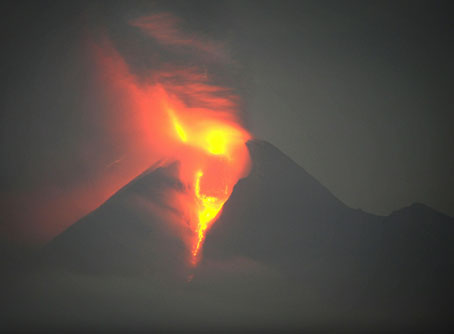 """Massive molten lava and searing ash clouds shoot from the crater of Mount Merapi captured in this extended time exposure photograph taken from Klaten district in Central Java province before dawn on November 4, 2010.  Thousands more people were evacuated from villages around Indonesia's Mount Merapi as the volcano erupts again, shooting ash and heat clouds high into the sky. The 2,914-metre (9,616-foot) Merapi, is a sacred landmark in Javanese culture whose name translates as """"Mountain of Fire."""""""