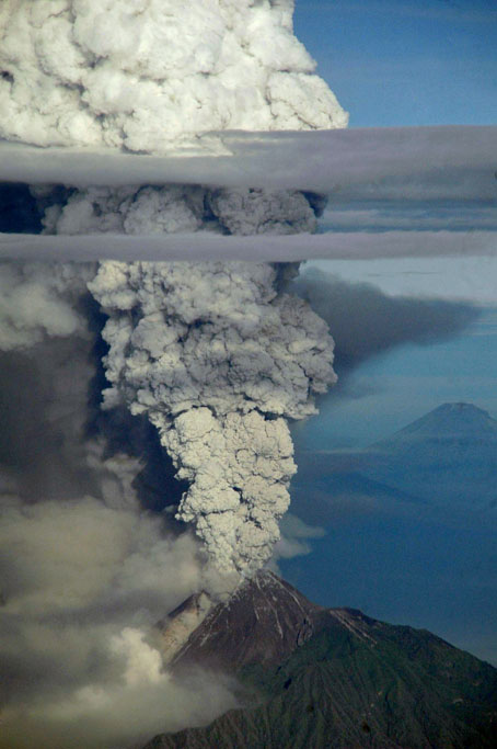 "A view from a domestic flight from Denpasar to Yogyakarta that was subsequently diverted to Surabaya airport shows a plume of gas and ash billowing some 10 km (six miles) high from the Mount Merapi volcano during an eruption on November 4, 2010. Volcanologists said the ""high intensity"" eruption was the strongest yet from the 2,914-metre (9,616-foot) Mount Merapi. Indonesia's most active volcano Merapi, located in Central Java province is a sacred landmark in Javanese culture whose name translates as ""Mountain of Fire."""
