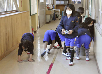 Extracurricular: Children clean a hallway covered with volcanic ash at their elementary school Monday in Takaharu, Miyazaki Prefecture. KYODO PHOTO-japantimes